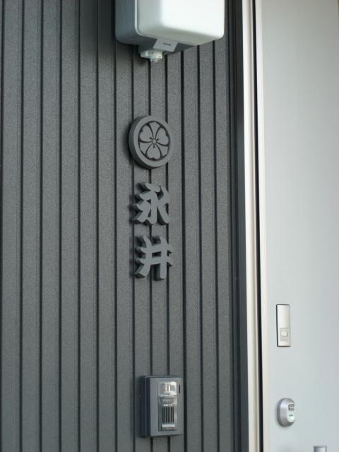 クラシカルな家紋と漢字を組み合わせたテラコッタの表札永井